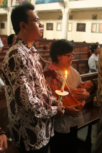 Ayah Anton hold Vian's baptism candle